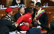 Venezuelan National Assembly president Diosdado Cabello (C) and security personnel restrain a man (red jacket) who suddenly approached Venezuelan President Nicolas Maduro (R) during his inauguration in Caracas, on April 19, 2013
