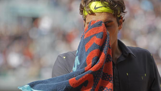 Roger Federer of Switzerland wipes his face in his semi final match against Novak Djokovic of Serbia at the French Open tennis tournament in Roland Garros stadium in Paris, Friday June 8, 2012. (AP Photo/Michel Spingler)