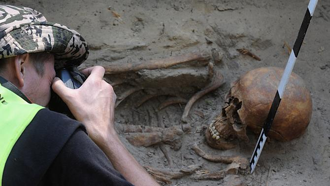 In this photo taken Tuesday, Aug. 7, 2012, an archeologist takes photos of a skull during works at the Powazki cemetery in Warsaw, Poland.  More than a hundred skeletons of Poles murdered by the communist regime after World War II have been excavated from a secret mass grave on the edge of Warsaw's Powazki Military Cemetery during recent digging works. Historians hope to identify among them the remains of Witold Pilecki who volunteered to be an Auschwitz inmate to secretly gather evidence of atrocities there. (AP Photo/Alik Keplicz)