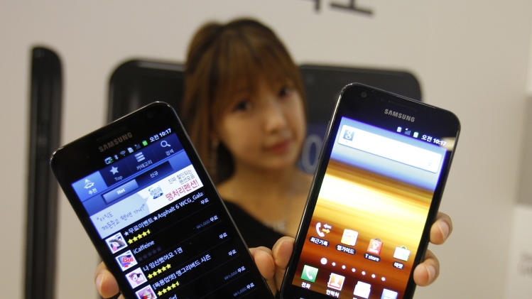 A model poses with Samsung Electronics' new smart phones Galaxy S II LTE, right, which features the 4.5-inch Super Amoled Plus screen and runs on the Android 2.3, and Galaxy S II HD LTE, which features the 4.65 HD Super Amoled screen and runs on the Android 2.3 during its unveiling ceremony in Seoul, South Korea, Monday, Sept. 26, 2011. (AP Photo/Lee Jin-man)