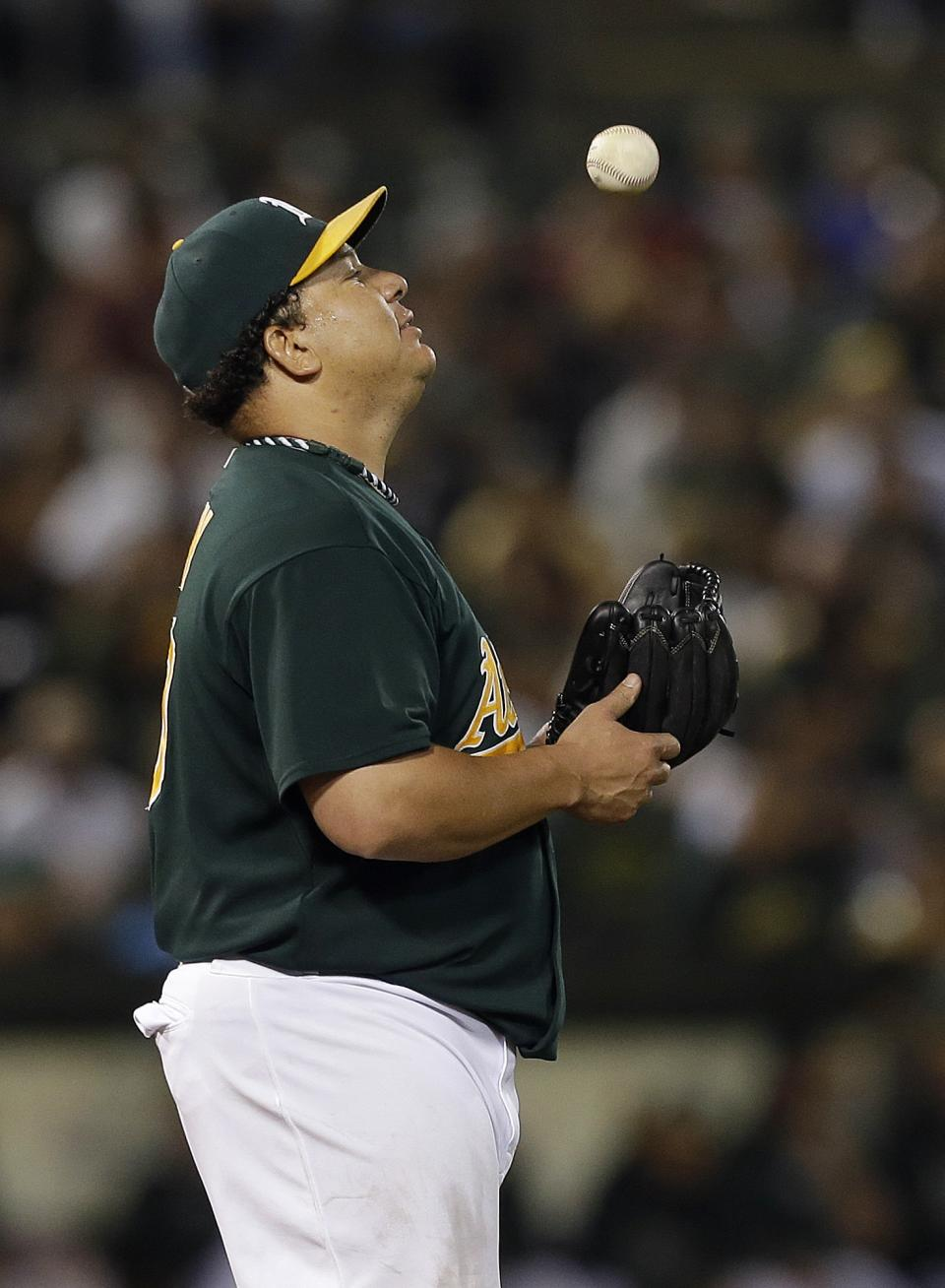 Oakland Athletics pitcher Bartolo Colon tosses the ball while standing on the mound during the fifth inning of a baseball game against the Texas Rangers in Oakland, Calif., Tuesday, Sept. 3, 2013. (AP Photo/Jeff Chiu)