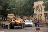 Soldiers loyal to Captain Amadou Haya Sanogo sit on an armoured vehicle at the Patrice Lumouda roundabout in Bamako last week. A month after handing power to civilians, Mali&#39;s ex-junta is resisting a return to barracks, threatening to disrupt a transition to democratic rule in Bamako while Islamists retain a firm hold on the north