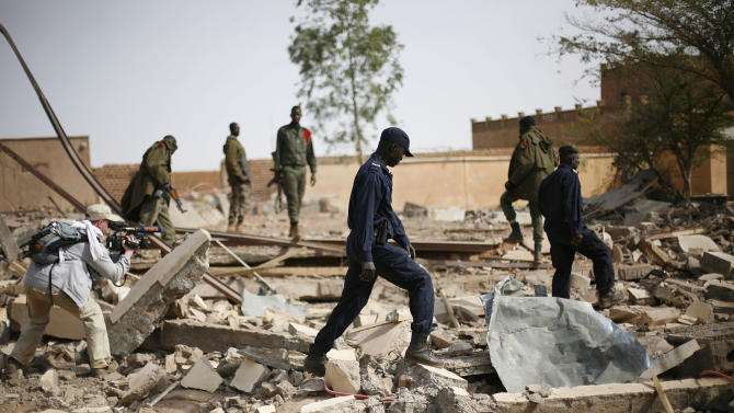 In this image taken during an official visit organized by the Malian army to the town of Konna, some 680 kilometers (430 miles) north of Mali's capital Bamako, Saturday, Jan. 26, 2013, a  videographer films Malian soldiers walking through the rubbles of a former army based leveled during fighting with islamist rebels. One wing of Mali's Ansar Dine rebel group has split off to create its own movement, saying that they want to negotiate a solution to the crisis in Mali, in a declaration that indicates at least some of the members of the al-Qaida linked group are searching for a way out of the extremist movement in the wake of French air strikes. (AP Photo/Jerome Delay)