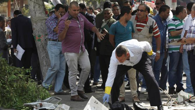Forensic workers and policemen carry out investigations at the scene of a bomb blast in Cairo