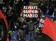 MILAN, ITALY - FEBRUARY 03:  Supporter of AC Milan holds up a banner showing his support of new signing Mario Balotelli during the Serie A match between AC Milan and Udinese Calcio at San Siro Stadium on February 3, 2013 in Milan, Italy.  (Photo by Claudio Villa/Getty Images)