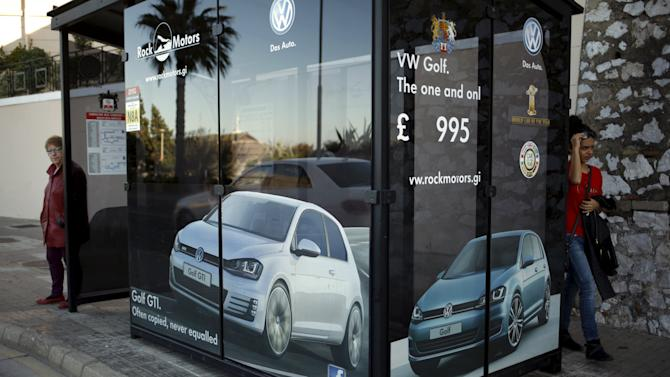 Women are seen next to an advertisement of Volkswagen Golf at a bus stop in the British colony of Gibraltar
