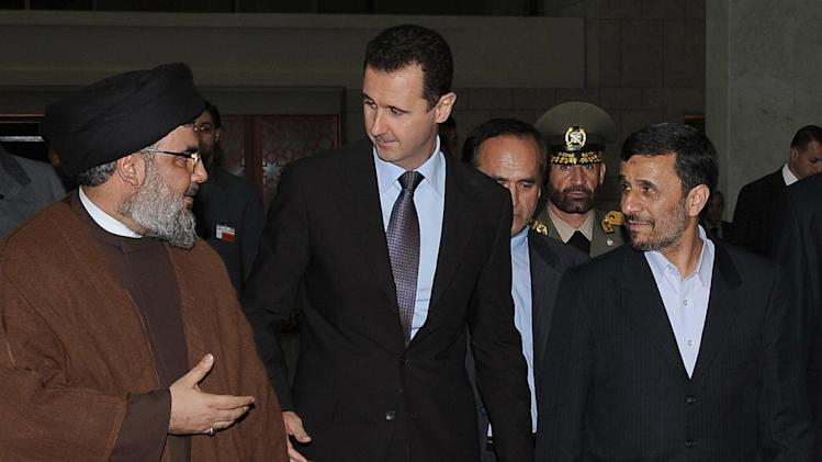 """FILE -- In this Thursday February 25, 2010 file photo, released by the Syrian official news agency SANA, Hezbollah leader sheik Hassan Nasrallah, left, speaks with Syrian President Bashar Assad, center, and Iranian President Mahmoud Ahmadinejad, right, upon their arrival for a dinner, in Damascus, Syria. The powerful alliance of Iran, Syria and militant groups Hezbollah and Hamas, once dubbed the """"Axis of Resistance,"""" is fraying. Iran's economy shows signs of distress from nuclear sanctions, Syria's president is fighting for his survival, Hezbollah is under fire by Lebanese who blame it for the assassination of an anti-Syrian intelligence official and Hamas _ the Palestinian arm _ has bolted. (AP Photo/SANA, File)"""