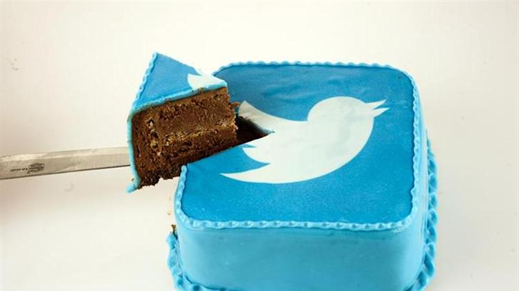 A person takes a slice of cake which is decorated in blue icing sugar with a Twitter logo at a bakery in Skopje, in this picture illustration taken September 10, 2013. REUTERS/Ognen Teofilovski/Files