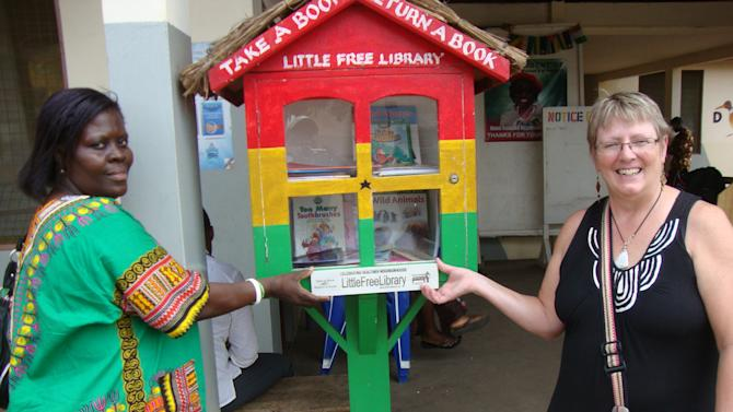 "In this Nov. 17, 2012 photo provided by Kathy Stutzman, Stutzman, right, and Antoinette Ashong, left, the head mistress of a girls' school in Accra, Ghana  pose by a ""Little Free Library"" in Accra. Ashong led an effort that has put up more than 50 little libraries in Ghana. (AP Photo/Kathy Stutzman)"