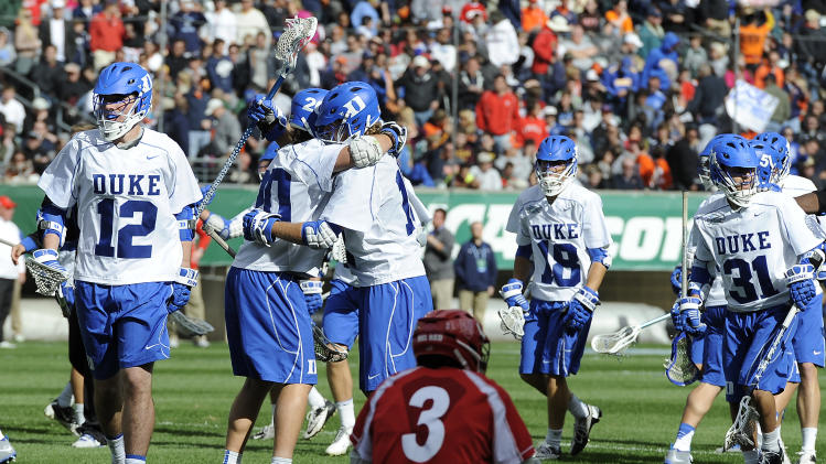 Cornell's Rob Pannell (3) watches Duke's Charlie Payton, left, and Chris Hipps, right, celebrate at the end of an NCAA college Division 1 semifinal lacrosse game on Saturday, May 25, 2013, in Philadelphia. Duke won 16-14. (AP Photo/Michael Perez)