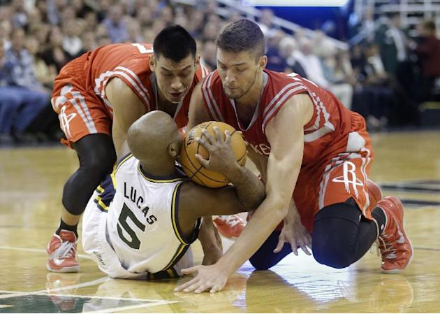 Utah Jazz's John Lucas III (5) battles with Houston Rockets Jeremy Lin, left, and teammate Chandler Parsons, right, for a loose ball  in the fourth quarter during an NBA basketball game Saturday, Nov.