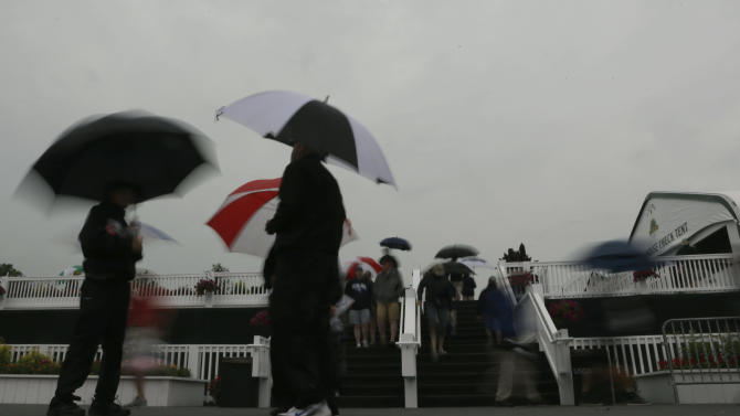 Spectators wait out a weather delay during the first round of the U.S. Open golf tournament at Merion Golf Club, Thursday, June 13, 2013, in Ardmore, Pa. (AP Photo/Morry Gash)
