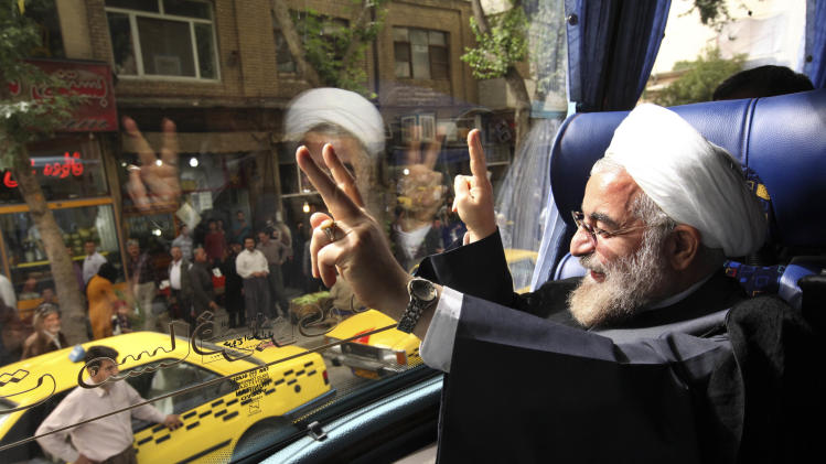 "In this Monday, June 10, 2013 photo, Iranian President elect, Hasan Rouhani, a former Iran's top nuclear negotiator, waves, from his bus, during his presidential election campaign tour to the western city of Sanandaj, Iran. Just a week before Iran's election gatekeepers announced the presidential ballot, Rouhani described the U.S. as the world's ""sheriff"" and said direct talks with Washington are the only way for breakthroughs in the nuclear standoff. (AP Photo/Vahid Salemi)"