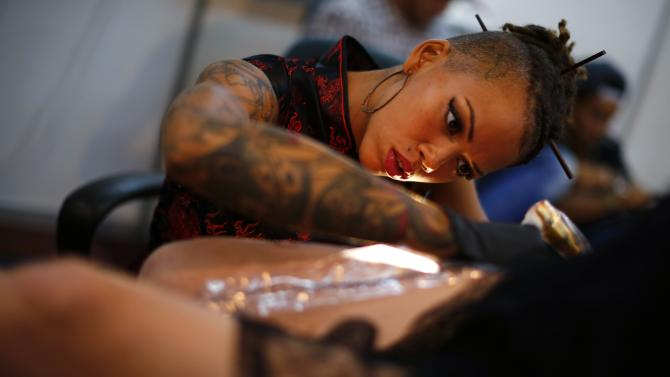 Woman is tattooed at Venezuela Expo Tattoo in Caracas