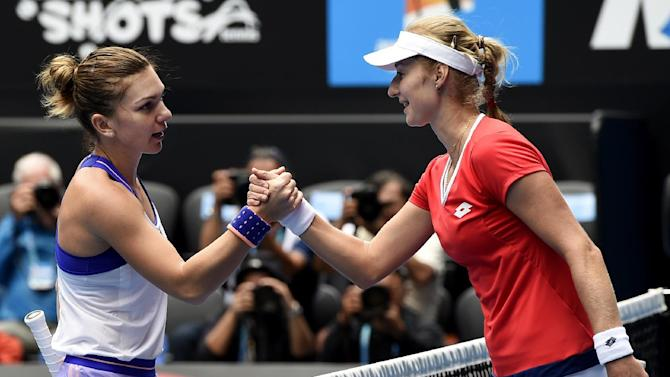 Ekaterina Makarova of Russia right, shakes hands with Simona Halep of Romania after winning their quarterfinal match at the Australian Open tennis championship in Melbourne, Australia, Tuesday, Jan. 27, 2015. (AP Photo/Andy Brownbill)