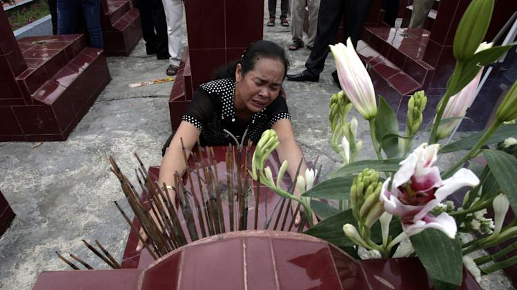 In this  Friday, Sept. 21, 2012 photo, Vu Thi Tuyen cries at the grave of her father Vu Dinh Doan at a cemetery in northern province of Hai Duong, Vietnam. Tuyen was a toddler when her father was killed fighting the American army in its doomed campaign in Vietnam. On Friday, the family was handed a wartime diary written by his father that had been returned by the United States. The pocket-sized book was originally brought to Vietnam in June by U.S. Defense Secretary Leon Panetta, who was handed a bundle of letters written by an American soldier that had been kept in Vietnam in an exchange that symbolized closer ties between the two nations. (AP Photo/Tran Van Minh)