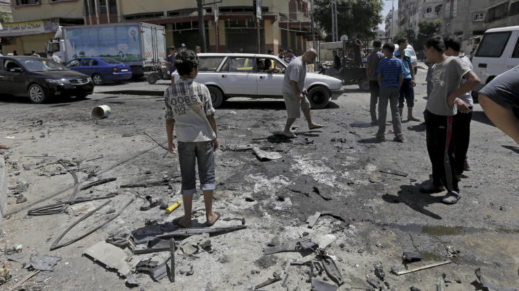 Palestinians search the site of the wreckage of a vehicle following an Israeli airstrike at the main street in Gaza City in the northern Gaza Strip, Thursday, Aug. 21, 2014. At least two were killed in the car outside a grocery shop, and a few others were wounded by an Israel airstrike on a Gaza City street, according to the Palestine Red Crescent Society. (AP Photo/Adel Hana)