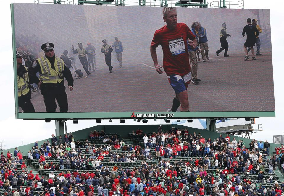 Scenes from the Boston Marathon bombings is displayed on an outfield screen before a baseball game between the Boston Red Sox and the Kansas City Royals in Boston, Saturday, April 20, 2013. (AP Photo/Michael Dwyer)