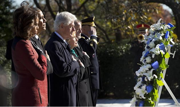 President Barack Obama, first lady Michelle Obama, former President Bill Clinton and his wife, former Secretary of State Hillary Rodham Clinton, pause during a wreath laying ceremony in honor of Presi