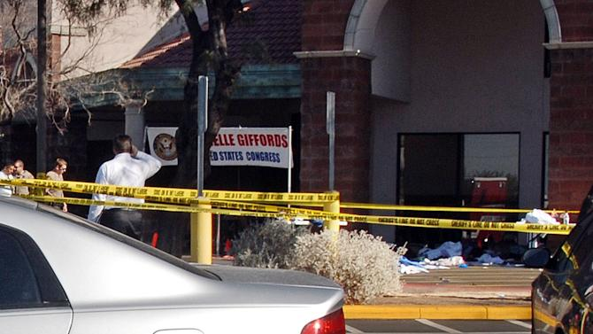 In this image released by the Pima County Sheriff's department, officials, left, and triage debris, lower right, are seen in the aftermath of the Tucson shooting rampage that killed six people and wounded former U.S. Rep. Gabrielle Giffords and 12 others in January 2011.  At far left a sign showing Giffords event can be seen. Authorities released more than 300 photos on Tuesday, May 21, 2013, made by investigators during their investigation in the parking lot of the shopping center where the shooting took place.  (AP Photo/Pima County Sheriff)