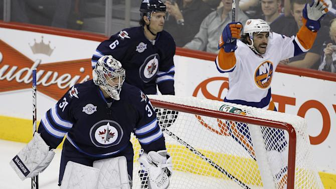 New York Islanders' Matt Moulson (26) celebrates behind the Winnipeg Jets' net after P.A. Parenteau opened the scoring, while Winnipeg Jets goaltender Ondrej Pavelec (31) and Jets' Ron Hainsey (6) look on during the first period of an NHL hockey game in Winnipeg, Manitoba, Tuesday, Dec. 20, 2011. (AP Photo/The Canadian Press, Trevor Hagan)