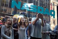 People look into the window of the Nasdaq stock market moments before Facebook shares went public on May 18. A lawsuit against the Nasdaq exchange said its massive technical problems on the first day of Facebook trade on Friday also resulted in losses to investors