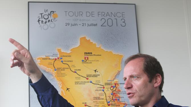 Tour De France Director Christian Prudhomme gestures as he speaks during an interview with the Associated Press in Issy les Moulineaux outside Paris, Tuesday, June 18, 2013. The road map of the 100th edition of the Tour de France 2013 is in the background. The Tour de France starts June 29 on the French Mediterranean island of Corsica. (AP Photo/Michel Euler)