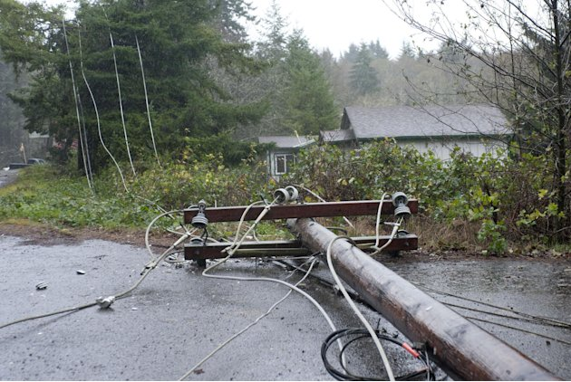 Utility pole and lines lie on the road north of Lincoln City, Ore., Monday Nov. 19, 2012 after being felled by trees knocked down by high winds.   A storm bearing down on the Pacific Northwest has tak