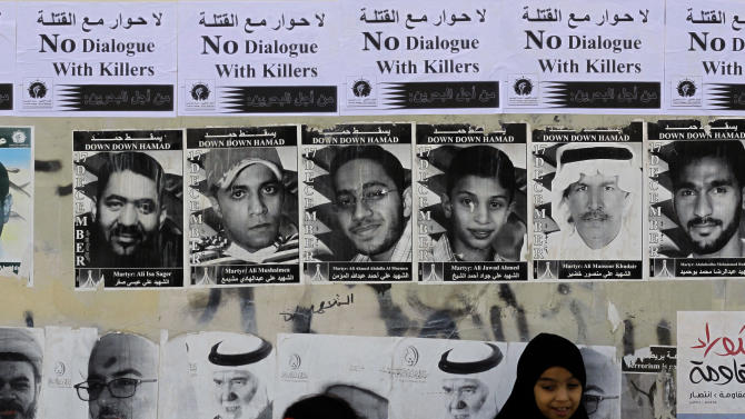Bahraini girls play by a wall covered with signs in English and Arabic objecting to a government-mediated dialogue scheduled for Sunday between opponents  and supporters of the Bahraini monarchy in Sitra, Bahrain, on Saturday, Feb. 9, 2013. Pictures on the wall are of those who have died in recent unrest and of prominent jailed opposition figures. (AP Photo/Hasan Jamali)