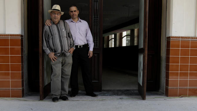 Jose Rafa Malem, 59, left, and Ernesto Iznaga pose for a photo in the entrance of Sloppy Joe's Bar in Havana, Cuba, Friday, Jan. 25, 2013. Sloppy Joe's will be reopened in February 2013 by the state-owned tourism company Habaguanex, part of an ambitious revitalization project by the Havana City Historian's Office, which since the 1990's has transformed block after block of crumbling ruins into rehabilitated buildings along vibrant cobblestone streets, giving residents and tourists from all over the chance to belly up to the same bar that served thirsty celebrities like Rock Hudson, Babe Ruth and Ernest Hemingway. (AP Photo/Franklin Reyes)