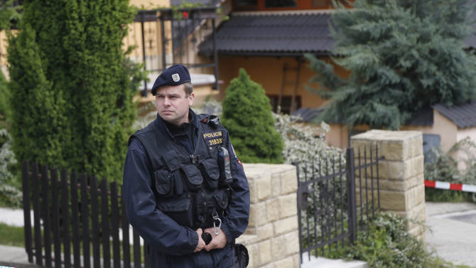 A police man stands guard in front of a crime scene in, Brno, Czech Republic, Thursday, May 23, 2013. An American man suspected of killing four people is on the run in the Czech Republic and likely armed, officials said Thursday. Brno Police spokeswoman Petra Vedrova identified the man as Kevin Dahlgren, born in 1992. (AP Photo/Petr David Josek)