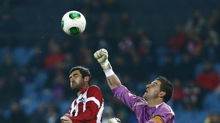 Sant Andreu's goalkeeper Pau Nunez, top right, in action with Atletico's Leo Baptistao, top left, during a Copa del Rey soccer match between Atletico de Madrid and Sant Andreu at the Vicente Calderon stadium in Madrid, Spain, Wednesday, Dec. 18, 2013