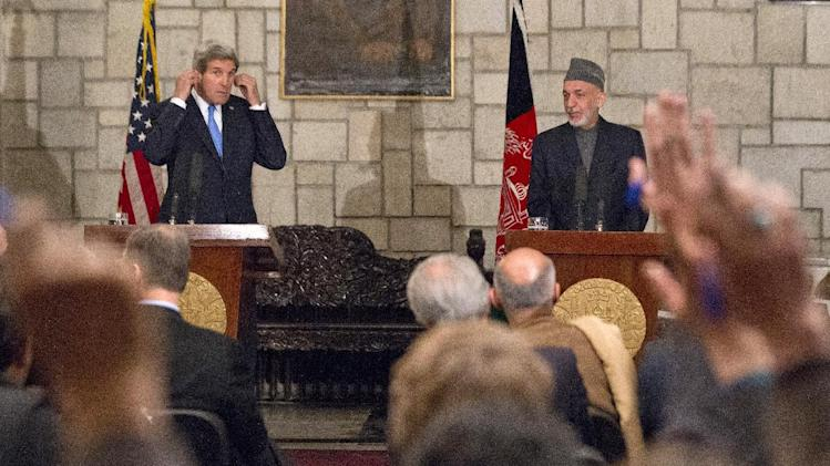 "Secretary of State John Kerry and Afghan President Hamid Karzai take questions during their joint newss conference at the Presidential Palace in Kabul, Monday, March 25, 2013. Kerry and Karzai made a show of unity Monday, shortly after the U.S. military ceded control of its last detention facility in Afghanistan, ending a longstanding irritant in relations between the two countries. Kerry, in Afghanistan for an unannounced visit, said he and Karzai were ""on the same page"" when it comes to peace talks with the Taliban. (AP Photo/Jason Reed, Pool)"