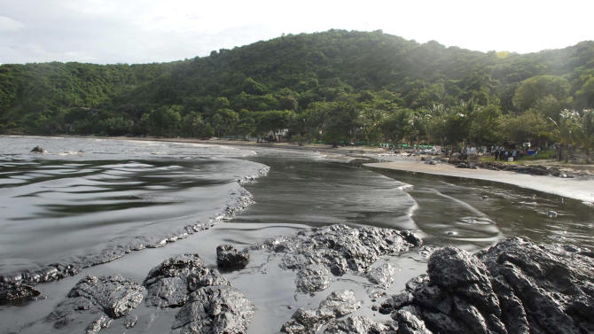 Streaks of crude oil cover the shore of Prao Bay on Samet Island in Rayong province eastern Thailand Monday, July 29, 2013. The oil spill that leaked from a pipeline has reached the popular tourist island in Thailand's eastern sea despite continuous attempts to clean it up over the weekend, officials said Monday. (AP Photo/Daily News) THAILAND OUT