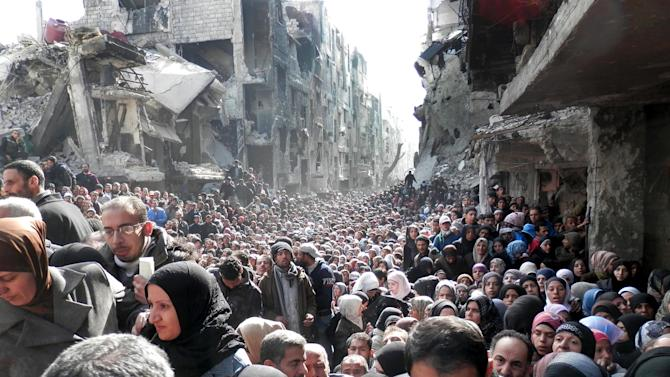 This picture taken on Jan. 31, 2014, and released by the U.N. Relief and Works Agency for Palestine Refugees in the Near East (UNRWA), shows residents of the besieged Palestinian camp of Yarmouk queuing to receive food supplies, in Damascus, Syria. A United Nations official is calling on warring sides in Syria to allow aid workers to resume distribution of food and medicine in a besieged Palestinian district of Damascus. The call comes as U.N. Secretary-General Ban Ki-Moon urged the Syrian government to authorize more humanitarian staff to work inside the country, devastated by its 3-year-old conflict. (AP Photo/UNRWA)