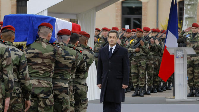 French President Nicolas Sarkozy stands by soldiers carrying a coffin during a ceremony to pay homage to the three soldiers killed by a suspect an Interior Ministry official identified as Mohammad Merah, claiming al-Qaida links, and also suspected in the killings of three Jewish children and a rabbi, Wednesday, March 21, 2012 in Montauban, southwestern France. Soldliers were Imad Ibn-Ziaten, 30, a paratrooper in the 1st Airborne Transportation Regiment based in Toulouse, Abel Chennouf, 25, who served in the 17th paratrooper combat engineering regiment based in Montauban and Mohamed Legouade, 26, the second paratrooper killed in the same shooting. (AP Photo/Jacques Brinon)