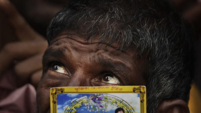 A Bangladeshi man holds a picture of a relative missing in a building that collapsed Wednesday hold pictures of loved ones at a makeshift morgue in a schoolyard in Savar, near Dhaka, Bangladesh, Saturday, April 27, 2013. Police in Bangladesh arrested two owners of a garment factory in a shoddily-constructed building that collapsed this week, killing at least 324 people, as protests spread to a second city Saturday with hundreds of people throwing stones and setting fire to vehicles. (AP Photo/Kevin Frayer)