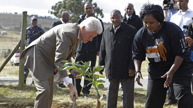 Former American president Bill Clinton, left, plants a tree to celebrate former South African president Nelson Mandela birthday in Qunu, South Africa, Tuesday, July 17, 2012. South African's will celebrate former president Nelson Mandela's birthday tomorrow. (AP Photo/Schalk van Zuydam)
