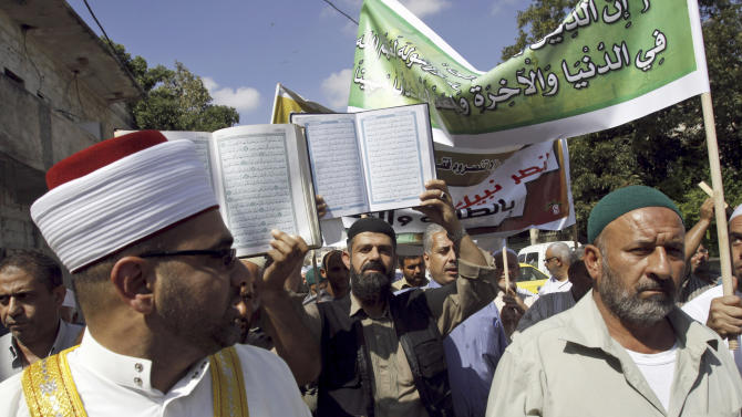 "Palestinian protesters hold copies of the Quran, the Muslim holy book, during a protest against the movie ""Innocence of Muslims"", in the West Bank town of Jenin, Thursday, Sept. 20, 2012, as part of widespread anger across the Muslim world about a film ridiculing Islam's Prophet Muhammad.(AP Photo/Mohammed Ballas)"