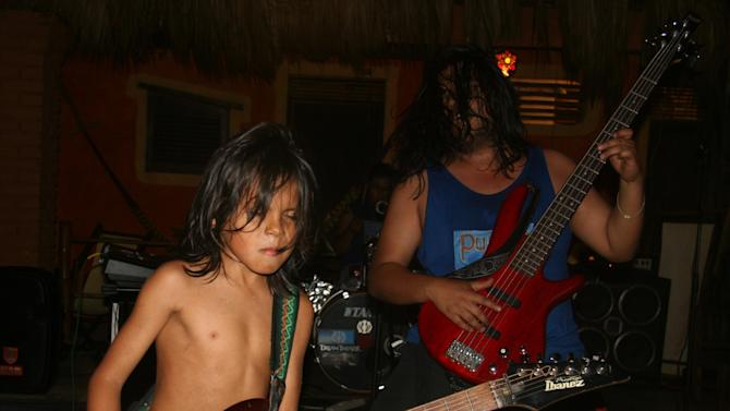 This Jan. 6, 2013 photo shows child guitar prodigy Cainn Cruz, left, performing at the Posada Mexico restaurant in Zipolite, Mexico. The ocean-front restaurant offers a variety of live entertainment.  A sleepy town with one main street and no ATMs, Zipolite is one many tiny coastal pueblos that dot the Pacific in Mexico's Southern state of Oaxaca. (AP Photo/Jody Kurash)