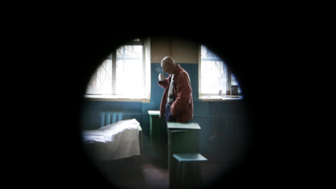 FILE - In this Tuesday, Nov. 20, 2012 file photo, a prisoner in a male prison is seen through a peephole where HIV-positive prisoners receive treatment, care and support in the town of Bucha outside Ukraine's capital Kiev. An estimated 230,000 Ukrainians, or about 0.8 percent of people aged 15 to 49 in a population of 46 million, are living with HIV, the virus that causes AIDS. Some 120,000 are in urgent need of anti-retroviral therapy, which can greatly prolong and improve the quality of their lives. But due to a lack of funds, less than a quarter are receiving the drugs, one of the lowest levels in the world. (Photo/Efrem Lukatsky)