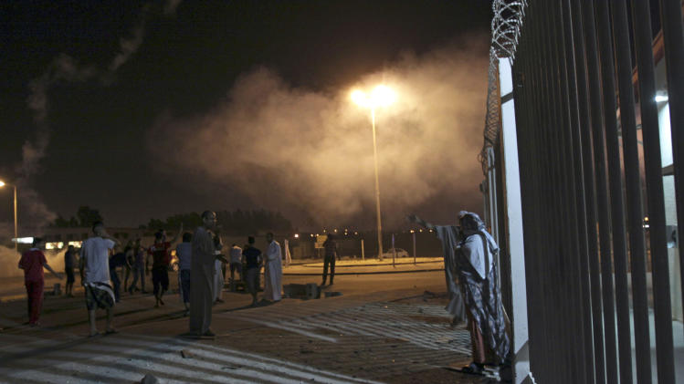 Bahraini villagers react to tear gas and stun grenades fired by riot police cordoning off the site in Sadad, Bahrain, early Saturday, Sept. 29, 2012, where a youth was killed during an anti-government protest, allegedly by police shotgun fire.  (AP Photo/Hasan Jamali)