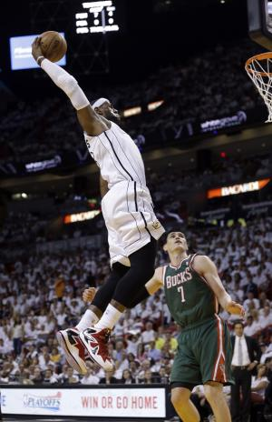 Miami Heat's LeBron James, top, goes to the basket as Milwaukee Bucks' Ersan Ilyasova (7) looks on during the first half of Game 1 of their first-round NBA basketball playoff series in Miami, Sunday April 21, 2013. (AP Photo/Alan Diaz)