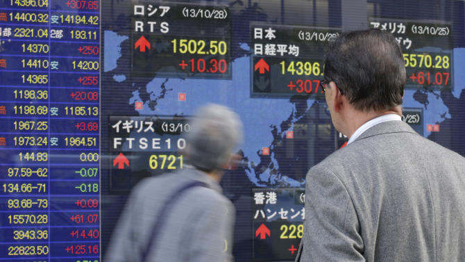 People watch an electronic stock indicator in Tokyo, Monday, Oct. 28, 2013. Asian stock markets were mostly higher Monday amid growing expectations that the U.S. Federal Reserve won't start reducing its monetary stimulus until at least the first quarter of next year. Japan's Nikkei 225 rose 1.8 percent to 14,340.01. (AP Photo/Shizuo Kambayashi)