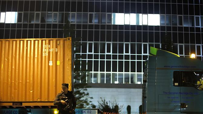 An armed police officer guards several trucks carrying containers after arriving at the country's Central Bank in Nicosia, Cyprus, on Wednesday, March 27, 2013. The contents of the trucks could not be independently confirmed, although state-run television reported they were carrying cash flown in from Frankfurt for the bank reopening.  (AP Photo/Petros Karadjias)
