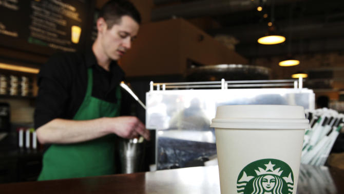 "FILE - In this Friday, April 27, 2012, photo, a Starbucks drink waits for a customer to pick it up as barista Josh Barrow prepares another at left  in Seattle. The world's biggest coffee chain is asking employees at cafes in the Washington, D.C., area to scribble the words ""Come Together"" on cups for drink orders on Thursday and Friday. CEO Howard Schultz says the words are intended as a message to lawmakers about the damage being caused by the divisive negotiations over the ""fiscal cliff."" It's the first time employees at Starbucks cafes are being asked to write anything other than customers' names on cups.  (AP Photo/Ted S. Warren, File)"