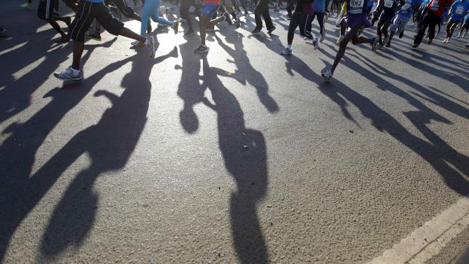 Runners cast shadows on the ground as they take part in the Standard Chartered Nairobi Marathon in Nairobi