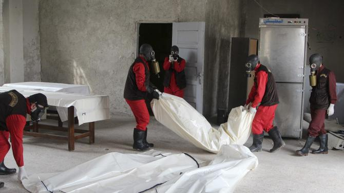 Workers wrap the bodies of dead fighters loyal to Syrian President Assad at a morgue in Aleppo