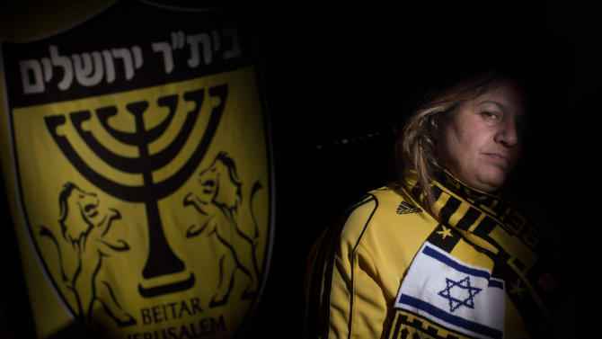 In this Tuesday, Jan. 29, 2013 photo, longtime soccer supporter of Beitar Jerusalem F.C., Abigail Sharabi poses for a portrait inside her home in the east Jerusalem neighborhood of Pisgat Zeev. The offices of the Beitar Jerusalem soccer team were set on fire early Friday in an apparent arson attack, police said, a day after four of the club's fans were charged with anti-Muslim chanting at a recent game. Tensions have been bubbling ever since the team announced last month it would sign on two Muslim Chechen players — Zaur Sadayev and Gabriel Kadiev — in a break from the team's unofficial tradition of not signing Arabs or Muslims. (AP Photo/Bernat Armangue)