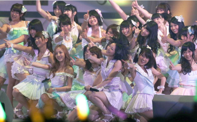 FILE - In this June 6, 2012 file photo, Japans all-girl pop idol group AKB48 members perform during the annual AKB48 popularity poll in Tokyo. More than 60 girls and young women, split into four team